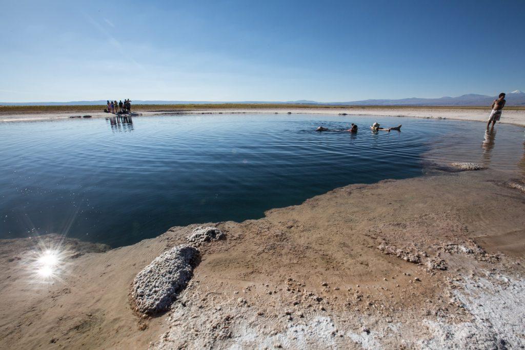 Swimming in the natural pool Salar de Uyuni Atacama Desert Chile by Nori Jemil