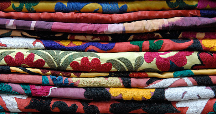 Stack of embroidered suzanis Uzbekistan Sophie Ibbotson and Max Lovell-Hoare